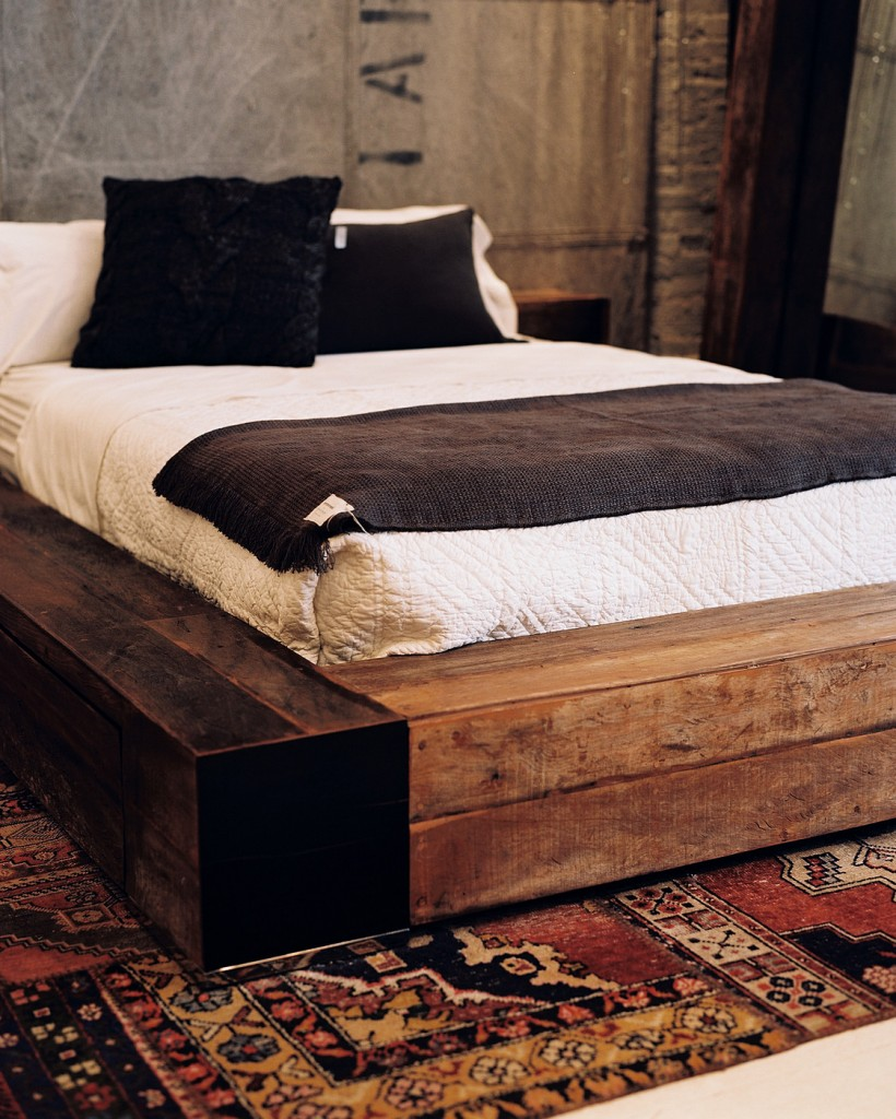 A wooden side table and bed atop a patterned rug