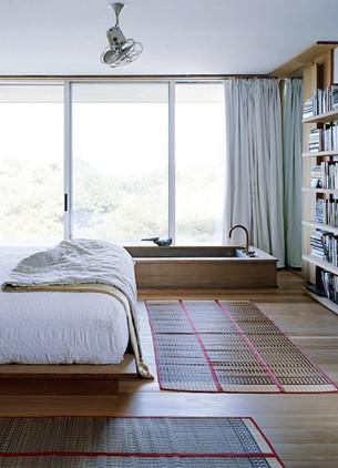 Simple bedroom with sunken wooden bathtub