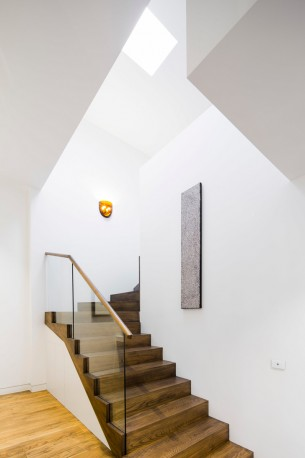 Wooden Staircase with Minimailist wall and skylight